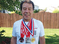 IMAGE Ray Fougnier (Wolf Clan) proudly wearing Powerlifting medals